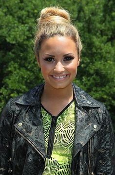 Demi Lovato smiles under her sky high bun.