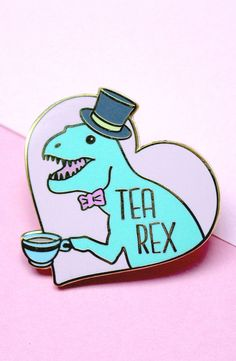 A hard enamel pin with a t-rex in a top hat holding a cup of tea, and the words 'Tea Rex'. wide with two pink pin clutches. Jacket Pins, Head Jewelry, Cool Pins, Hard Enamel Pin, Pin And Patches, Up Girl, Funny Pins, Pin Badges, T Rex