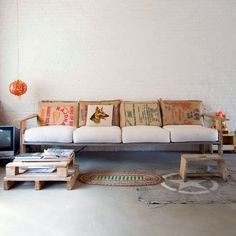 Get a few rice & coffee type of burlap sacks and make these sack pillows for accents-- This could make an amazing replacement for our back pillows. Looks just like our couch!