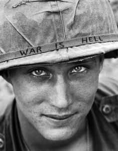 """An identified U.S. Army personnel wears a hand lettered """"War Is Hell"""" slogan on his helmet, June 18, 1965, during the Vietnam War. He was with the 173rd Airborne Brigade Battalion on defense duty at Phouc Vinh airstrip in South Vietnam. ("""