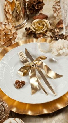Use my gold chargers, clear plates with black napkins under plate on top of chargers and tie gold ribbon around silverware
