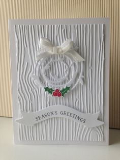 handmade Christmas card ... almost all white ... main panel with heavy embossing folder woodgrain lines ... wreath cut with Swirly Bird die ... sweet ribbon ... sentiment on die cut wavy banner ... only little holly berries and leaves in color ... Stampin' Up!