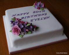 Classic 80th birthday cake with bright sugar paste flowers
