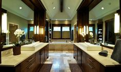 Rich+textures+define+this+symmetrical+bathroom,+from+dark+wood+and+marble+on+the+mirrored+vanities,+to+a+mixture+browns+on+the+marble+floor+tiles.+Vaulted+ceiling+is+defined+by+a+single+exposed+beam+running+length+of+the+room.