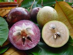 Star apple. To eat this, you have to knead the fruit until the inside is soft. The flesh is a deep purple, very sweet, jelly.
