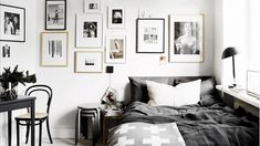 Gray and white bedroom featuring a gallery wall and small workspace