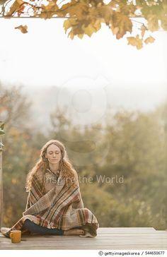 Woman practising yoga on wooden deck in Autumn - gettyimageskorea