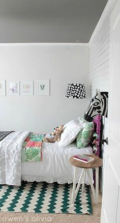 Adorable girl's bedroom with white wall paneling painted Benjamin Moore Decorator's White accented with Anthropologie Savannah Story Bust - Zebra over Target nightstand and Urban Outfitters Zigzag Rug.