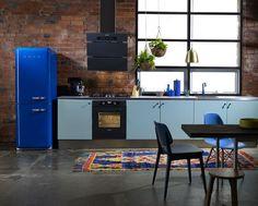 Cuisine au style industriel avec un mur en briques et un frigo bleu brut