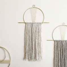 """Attalie Dexter  Brass 8"""" circle and flat vertical brass bar wall hanging with hanging yarn  in pale ivory and flax tones. The fiber is a mix of two textures, one soft  wool and one merino/alpaca/silk blend. The brass circle is partially  wrapped with hand-dyed waxed linen and attaches a small vintage brass loop  for hanging.  Total dimensions are 12"""" wide and 22"""" tall. The fringe extends 14-15"""" from  the brass bar."""