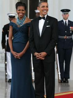 Michelle Obama impressed state-dinner guests on Wednesday, wearing a subtly ruched blue Marchesa gown with Tom Binns pearls while waiting with the president for the arrival of United Kingdom Prime Minister David Cameron and his wife, Samantha, on the White House's North Portico. Guests dined on bison Wellington and enjoyed performances by John Legend and British folk group Mumford & Sons.