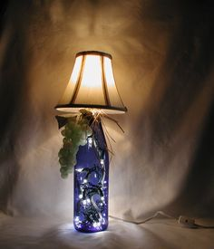 WINE BOTTLE TABLE LAMP.  Very eye-catching lamp made from a 750ml wine bottle with the label removed.  The bottle is cobalt blue and the lamp shade is cream.  Perfect gift for a wine lover - excellent housewarming present.   $30.00