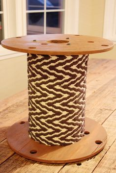 side table made out of a large spool and a rug, the rug details makes it look so good.
