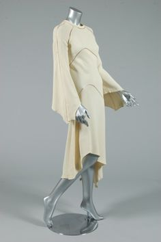Alice Pollock bias cut ivory ensemble, early 1970s, printed black on white satin label, the dress of moss crepe with curved faggotted seams and undulating hem; the jacket/blouse of silk crepe with similarly worked seams, full sleeves with ties to cuffs, satin piping and neck ties, buttoned waist