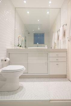 Banheiro todo branco, com estilo retrô! Piso com formato hexagonal, parede com pastilha retangular e espelho embutido.