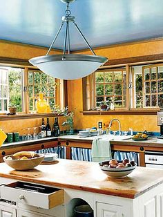 The kitchen feels extra warm and inviting with its orange walls and sky-blue ceiling. Though the center island is new, its wooden top, drawer pulls, and lines recall a vintage find. (Photo: Roger Davies)