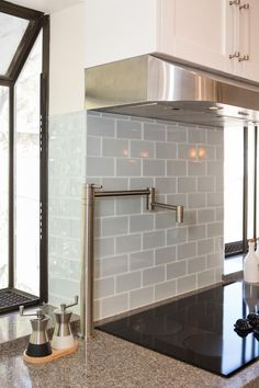 Light gray subway tile is the perfect complement to the darker gray granite countertops and white cabinetry in this bright and airy kitchen. Add some modern flare to our traditional cabinets.