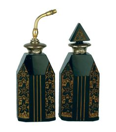 A pair of Art Deco black glass perfume bottles, each with incised and cut floral decoration with gilt embellishment, silver tops, one with glass stopper, the other with atomiser. London 1929 by Henry Perkins & Sons