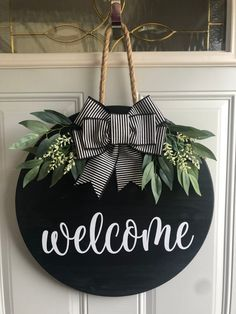 """•SIZE: 18"""" wood round door hanger; 1/2"""" thick. •DESIGN: The wood round choices are black, white. Coordinating wording to go with as shown in photos. The bow is black and white. Greenery is attached, as well as a rope to hang the round from. Please note: the back is not finished, if this is Welcome Signs Front Door, Front Door Decor, Door Hanging Decorations, Fall Door Hangers, Christmas Door Hangers, Wood Door Hanger, Wooden Wreaths, Door Wreaths, Wooden Door Signs"""