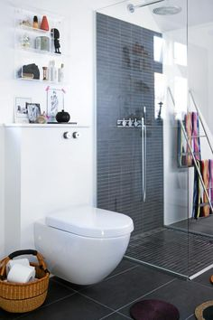 De mørke flisene på gulvet strekker seg oppover veggen i dusjen, og deler dermed opp rommet. Over toalettet er det festet hyller for oppbevaring av baderommets nødvendigheter, samt litt pynt.