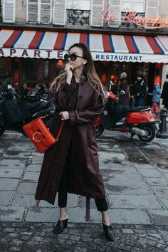 Fashion blogger Beatrice Gutu wearing burgundy leather trench coat with red J.W. Anderson pierce bag and leather mules trend outfit ideas