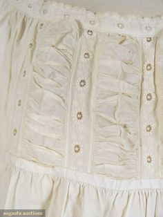 Detail of mid-19th-century cotton chemise with mysterious waist-level hemmed slit, as well as puffings and insertion. From the Tasha Tudor auction at Augusta Auctions.