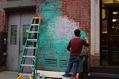 Beau Stanton starts the mural with a base layer of blue and white