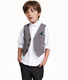 Gilet souple en twill de laine mélangée. Modèle avec boutonnage devant, poche de poitrine agrémentée d'une pochette décorative et fausses poches devant. Patte décorative avec boucle en métal dans le dos. Doublé.