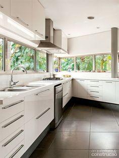 Compacta e inserida num canto, a cozinha traz janelas nas duas paredes em ângulo para boa luminosidade. Projeto Shieh Arquitetos Associados.