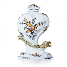 Perfume bottle in faience, 18th century. Glazed faience, 18th century, floral polychrome decoration, shape of a heart with a double-headed serpent.