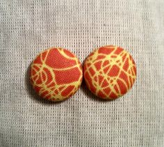 Handmade fabric covered earrings featuring an orange/yellow squiggle pattern.