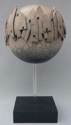 Keramieke bol rondom met huizen, op voet met pen van plexieglas.