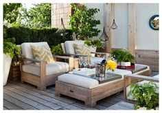 Kick up your feet and relax in this gorgeous deck boasting facing weathered teak chairs topped with yellow zebra pillows facing a weathered teak ottoman used as a coffee table illuminated by black wire lanterns.