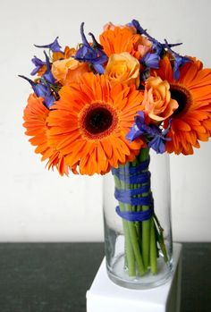 Bridal Bouquet of orange gerbera daisies, blue delphinium and orange roses.
