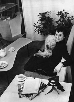 Florence Knoll and her dog Cartree, enjoying a spot of tea, beside a stabile by Alexander Calder, a coffee table by Alexander Girard, and a Butterfly Lounge Chair by BKF.