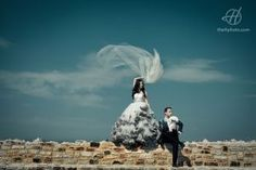 Bride and Groom posing on a fortress wall.  Blue sky in background