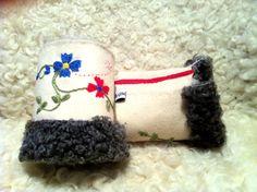 Varma broderade handledsvärmare i fårskinn och kläde.   Ängsdesign