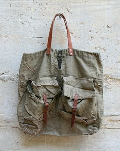 Czech military vintage canvas tote  Handmade by a guy with the initials FG. These bags are made with vintage Czech military knapsacks. Like the helmet bag but with leather straps and leather strap closures for the front pocket. Has 2 metal rings on the bottom and 5 cloth loops on the back and sides. Also has a large second compartment inside
