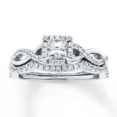 A princess-cut diamond is traced in round diamonds to form the brilliant center of her engagement ring, in this pretty bridal set for her. The 14K white gold band features intertwining waves — one lined in additional round diamonds — while the matching wedding band is contoured and lined with round diamonds to complement. The bridal set has a total diamond weight of 3/4 carat. Diamond Total Carat Weight may range from .69 - .82 carats.