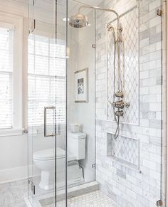 Faux marble tile inside shower, white hexagon tile on bottom of shower, clear glass shower doors