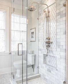 Faux marble tile inside shower, white hexagon tile on bottom of shower, clear glass shower doors