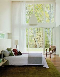 a wall of windows, is my dream. A beautiful view is my dream. I like the green rug it reminds me of grass.