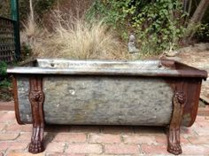 Vintage rustic iron bath, with detailed claw feet.