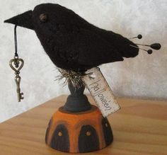 Halloween Crow.  Handstitched wool. Hand painted wooden stand. Stick pin tail feathers. Holds Metal key charm. Accented with tinsel trim.