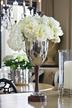 Those white carnations look so beautiful in this high-stem trophy vase.