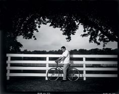 """Ali's home, Berrien Springs, Mich., 1996  -  Walter Iooss Jr.: """"I wanted to do an Annie picture that day — Annie Leibovitz, that is. As we drove into his estate, the fence was the first thing to catch my eye, but I wasn't sure how to incorporate it into a photograph. Then Ali came out on a bike, and the image came together. Serendipity at its best."""" Walter Iooss Jr. is a Sports Illustrated photographer."""