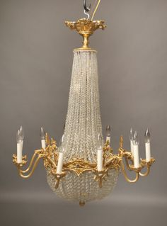 Late 19th Century Gilt Bronze and Beaded Crystal Basket Twenty Light Chandelier.  Very finely casted bronze arms supporting ten perimeter li...
