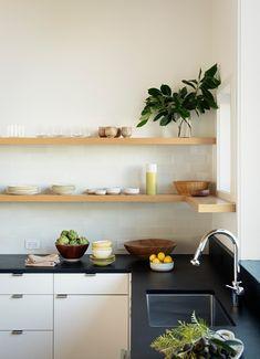 white kitchen cabinets, black countertops, wood open shelving