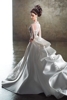 Romance + elegance abound in this astounding creation from Reem Acra, one of the leading ladies of luxury bridal wear. Reem Acra® Bride Barbie® is stunning in a satin gown adorned with the designer's signature beading + embroidery. The train is complete with intricate bustling + details, making dress a show stopper in every sense! Accoutrements include simple pearl studs + tiara accenting the doll's sleek up do, allowing the gown to shine on its own. Romantic, unique + overwhelmingly chic.