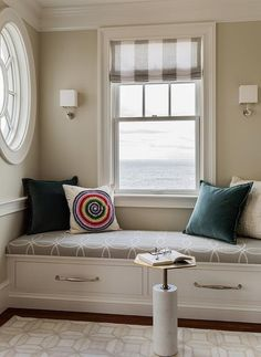 Living room reading nook features a built-in window seat fitted with drawers topped with a gray interlocking circles cushion placed under window dressed in a white and grey striped roman shade alongside a marble and brass accent table.